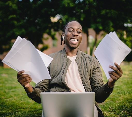 Happy man with laptop and papers
